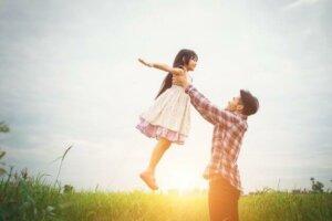 far som holder datteren opp i lufta på en blomstereng