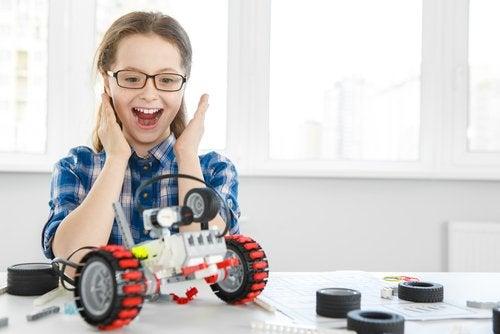 Ei jente som er fornøyd med en robot hun har bygget