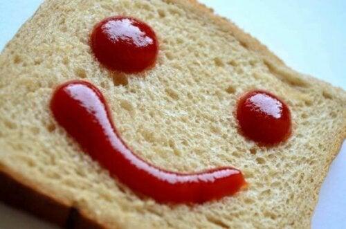 En brødskive med smilefjes av ketchup på