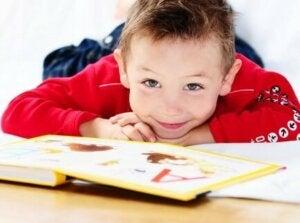 En gutt som leser en bok på gulvet
