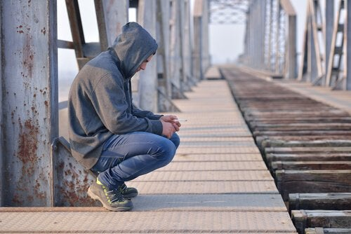 En ungdom som sitter på en bro med hette på hodet