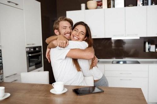 Et lykkelig par som holder rundt hverandre og smiler