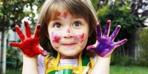 Liten jente som har maling på hendene og i ansiktet