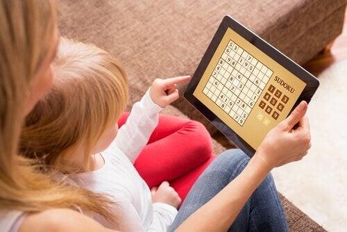 Mor og barn som sitter med et nettbrett og spiller sudoku