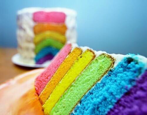 en fargerik kake som det har blitt skåret et stykke av