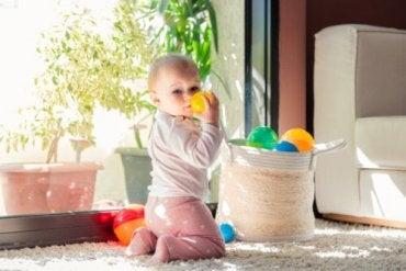 En baby som leker med leker fra en kurv