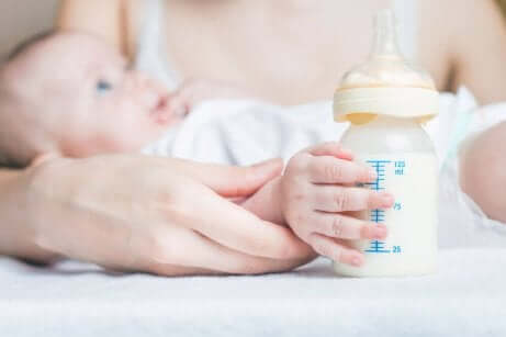 En baby som ligger på armen til moren sin og får flaske
