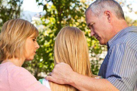 En familie som holder rundt tenåringsdatteren sin
