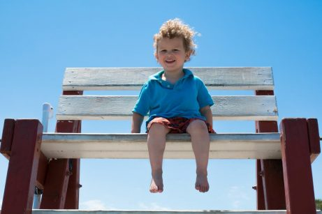 En liten gutt som sitter på en stor krakk