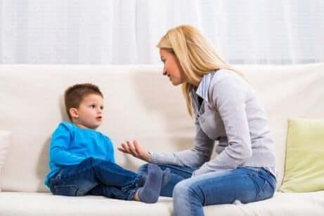 En mor som snakker med barnet sitt i sofaen