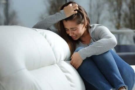 En tenåringsjente som gråter i en sofa