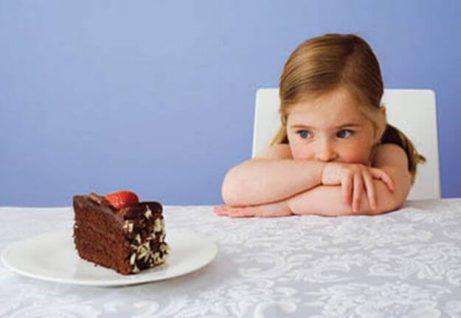 Et lite barn som ser på et kakestykke