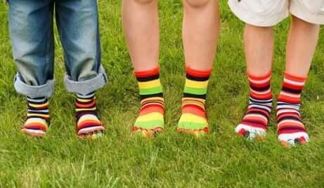 Føttene til tre barn med fargerike sokker på