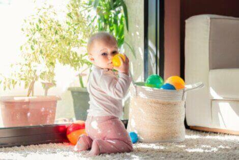 Baby leker med baller i en kurv