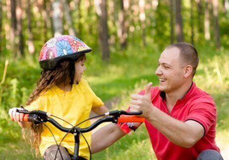 Ei lita jente som lærer å sykle sammen med faren sin