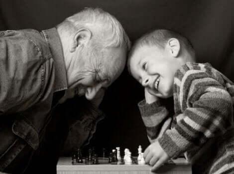 En gammel mann som spiller sjakk med et barn