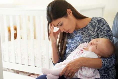 En kvinne sitter med babyen sin og er deprimert