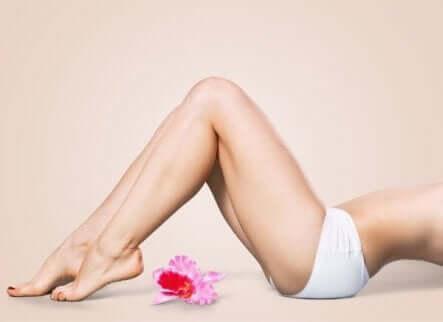 En kvinnelig underkropp som ligger i et rosa rom med en blomst ved siden av seg.