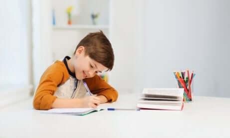En liten gutt som sitter ved en skrivepult