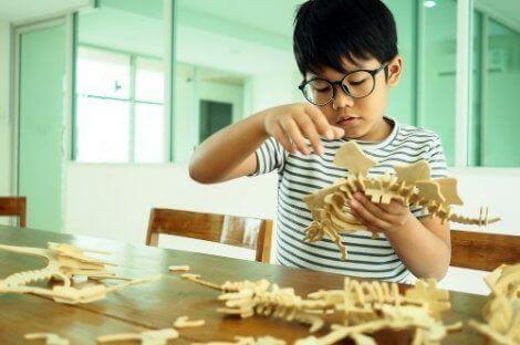 Et barn som bygger en dinosaurus