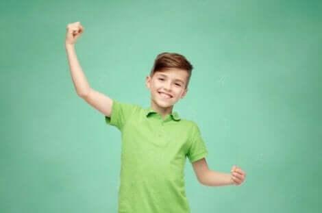 Et barn som flekser bicepsen og smiler