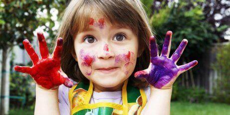 Et barn som har maling på hendene og i ansiktet