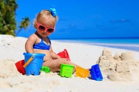 Et barn som leker med bøtte og spade på stranda