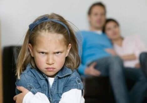 Ei sint jente med foreldrene i bakgrunnen