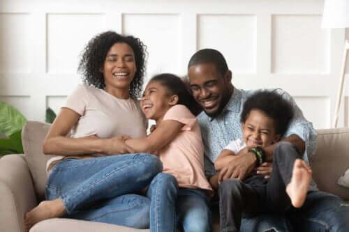 En familie som sitter i en sofa og ler sammen