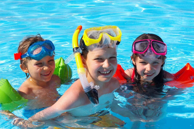 Barn som leker i et basseng med snorkelutstyr