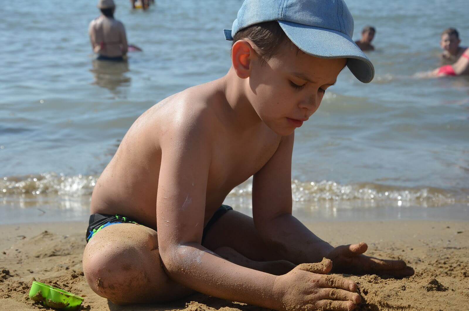 Et barn som leker i sanden på stranden