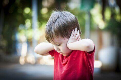En liten gutt som holder seg for ørene