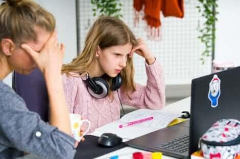 En mor som sitter og prøver å hjelpe tenåringen sin med lekser