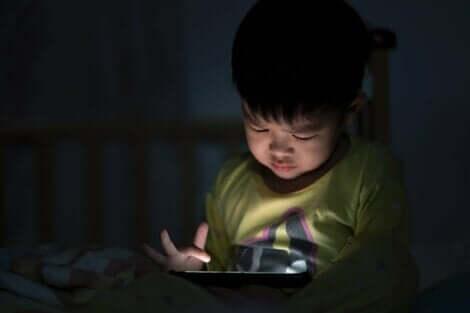Et barn som sitter med et nettbrett