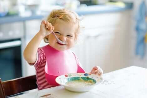 Et barn som sitter ved bordet og spiser