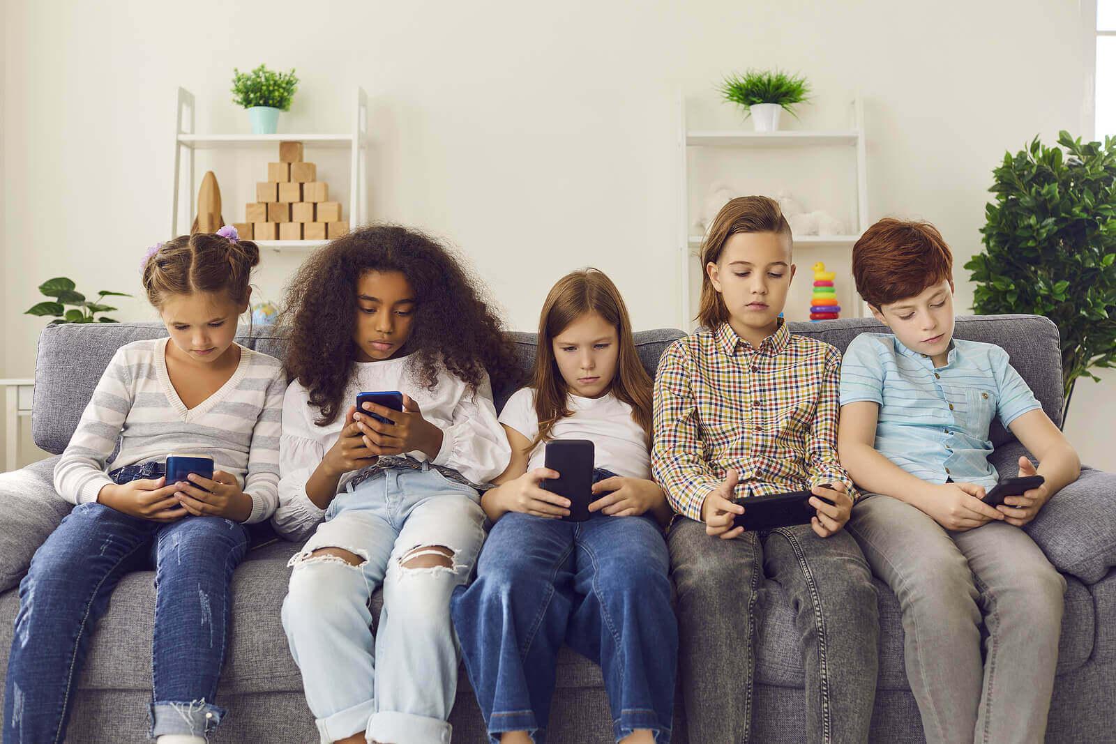 Fem barn som sitter i sofaen og ser på telefonene sine