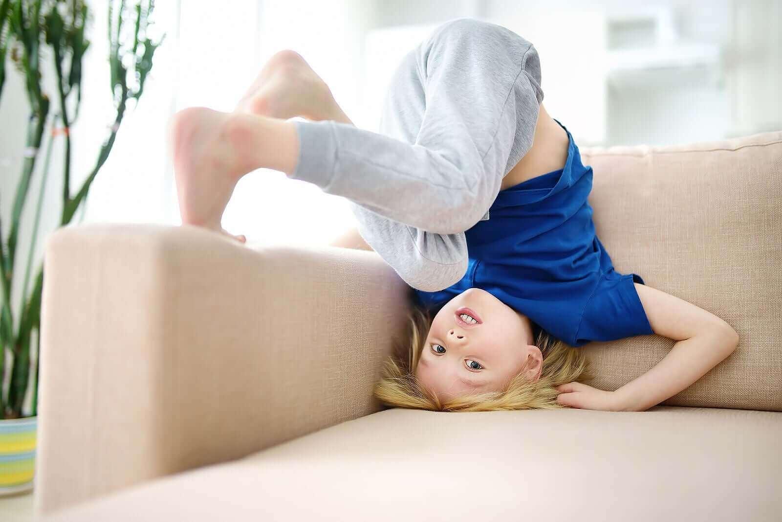Et barn som stuper kråke i en sofa