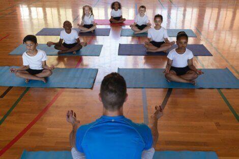 Barn som praktiserer yoga i en gymsal.
