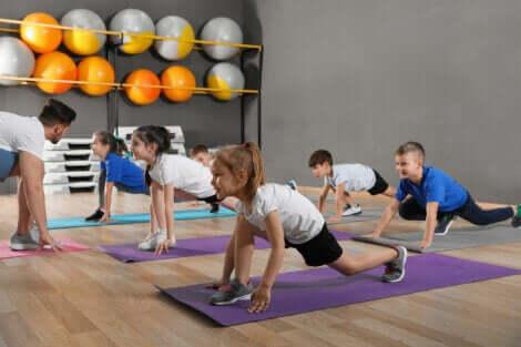 Barn som strekker seg på yogamatter i et treningsstudio.
