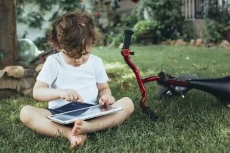 Et barn som sitter ute og leker med et nettbrett