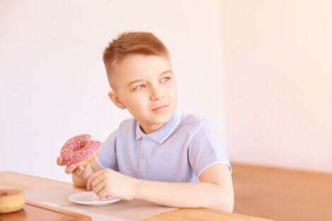 Et barn som spiser en donut.
