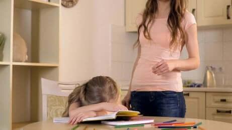 Et barn som ligger med hodet på bordet