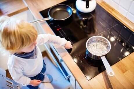 Et barn som står ved kasserollene på komfyren.