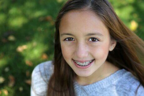 Jente med tannregulering som smiler.