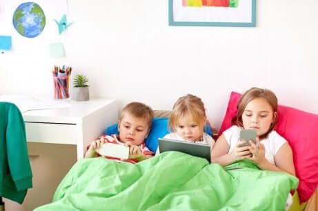 Tre barn som ligger i en seng og spiller spill