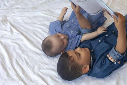 et søskenpar som leser bok i sengen